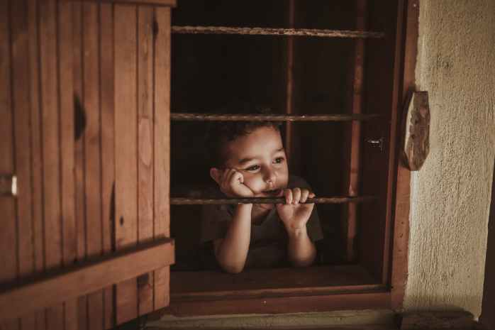 photo of boy leaning on window rails